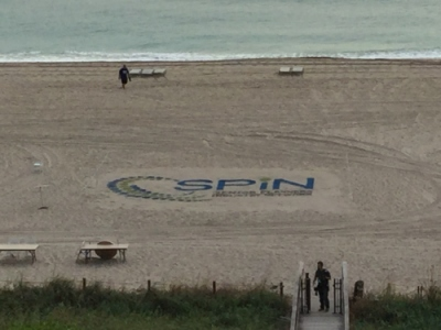 The SPIN Logo in the sand